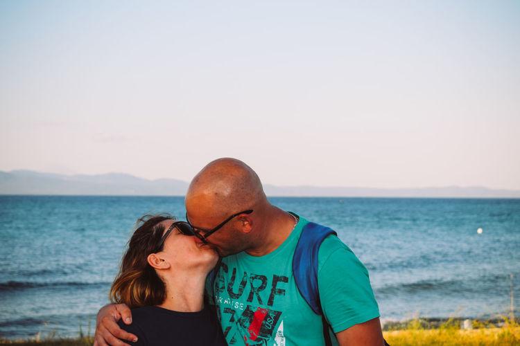 Couple kissing against sea