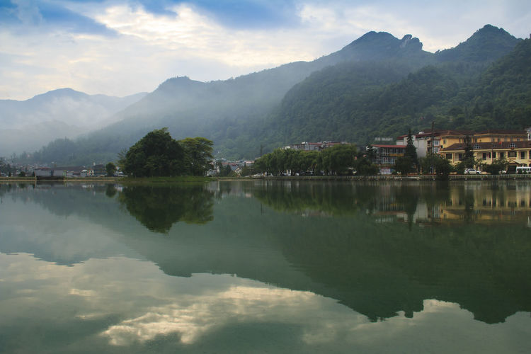 Scenic View Of Lake By Buildings And Mountains Against Sky