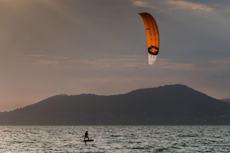 Person kitesurfing at sunset