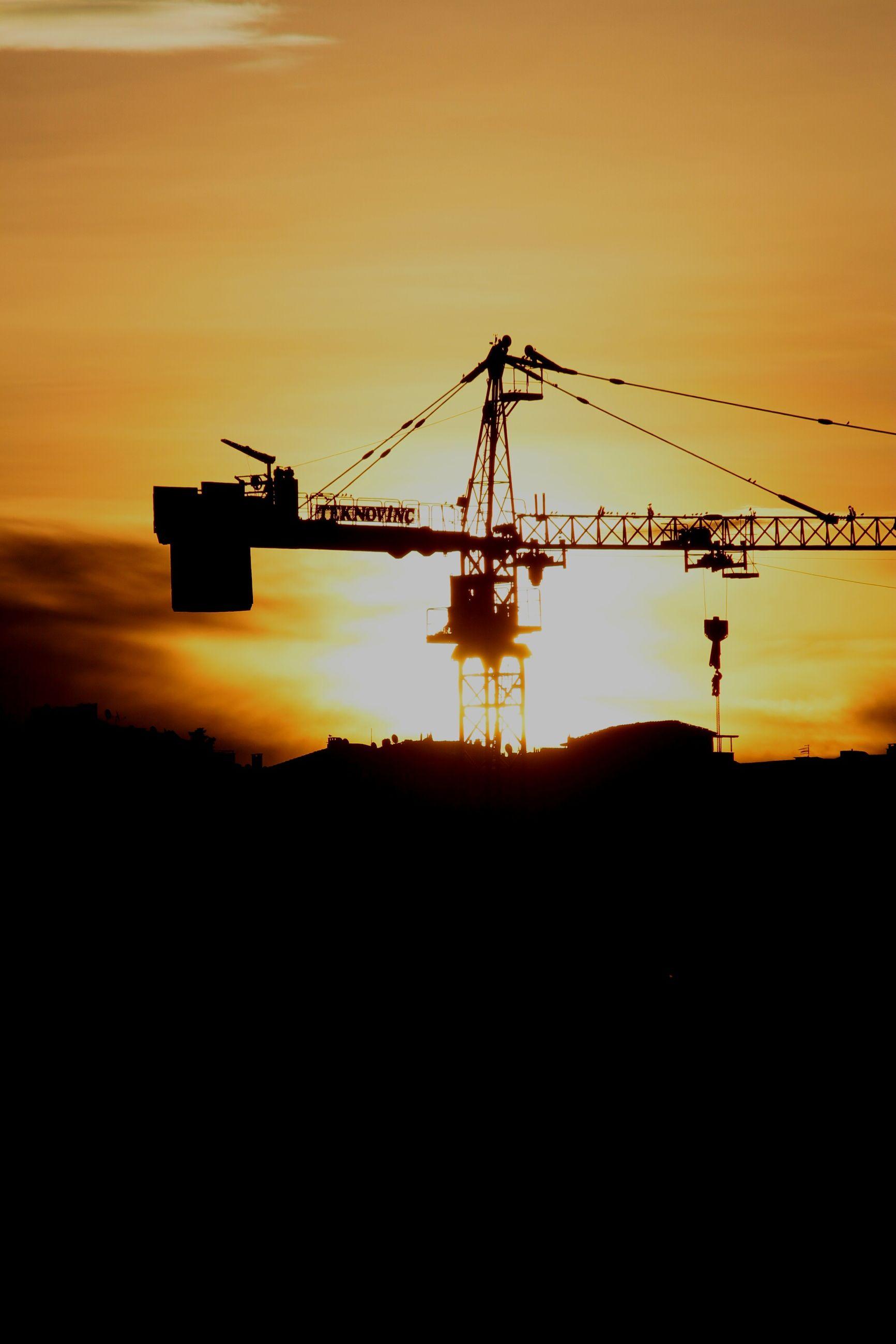 sunset, silhouette, orange color, crane - construction machinery, construction site, industry, sky, crane, sun, built structure, construction, development, beauty in nature, copy space, nature, fuel and power generation, architecture, scenics, dark, outdoors