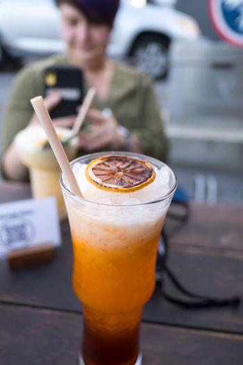 Woman photographing drink served on table