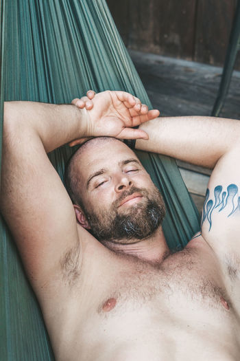 Relaxing in a hammock Lying Down Shirtless Men Relaxation Eyes Closed  Portrait Lying On Back Lifestyles Real People Headshot Front View People Beard Facial Hair Tattoo Adult Leisure Activity Young Adult Mature Men Hands Behind Head The Portraitist - 2019 EyeEm Awards