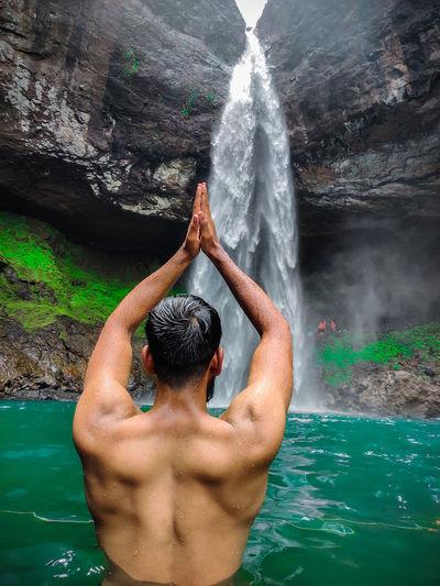 Rear view of shirtless man looking at waterfall