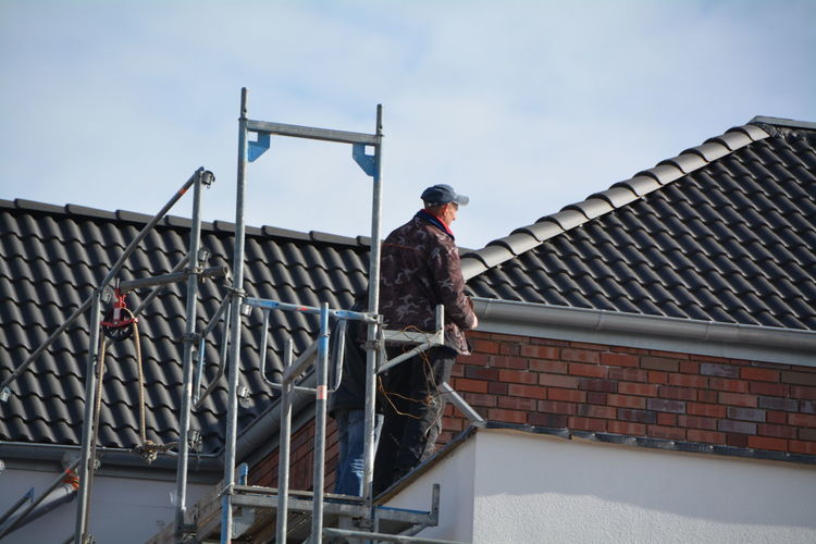Workers standing on platform by roof of house