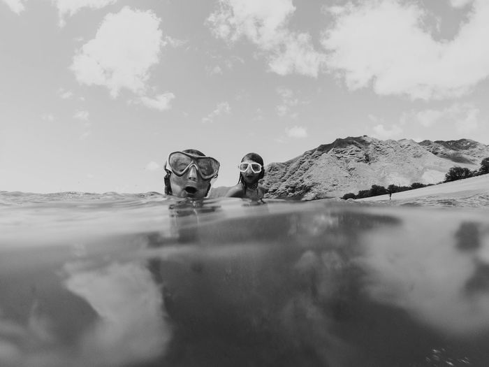 Portrait of people in water against sky
