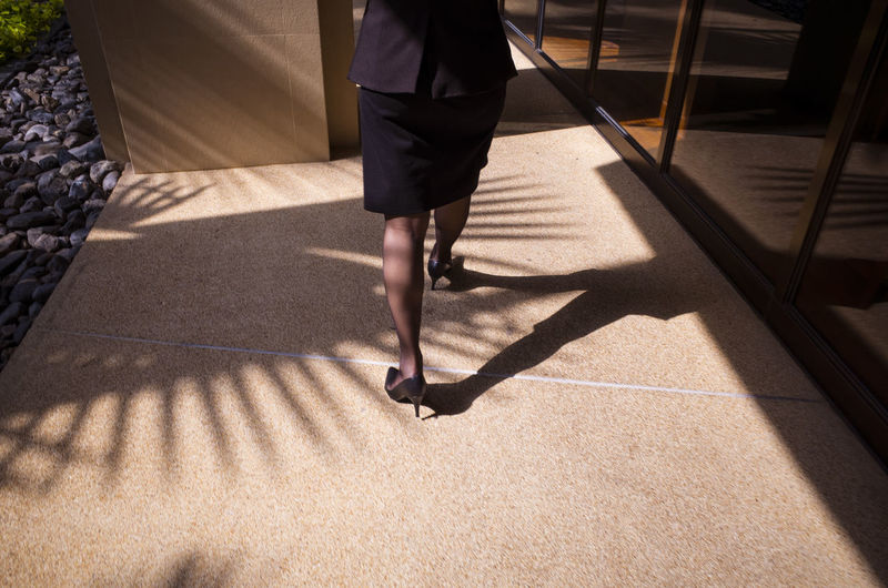 Low section of woman walking in corridor during sunny day
