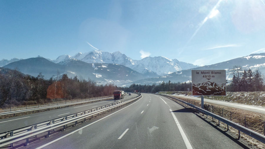 Mountain Transportation Road Sign Mountain Range Direction The Way Forward Sky Beauty In Nature Snow Scenics - Nature Nature Symbol Cold Temperature Day Winter No People Mode Of Transportation Sunlight Snowcapped Mountain Diminishing Perspective Dividing Line