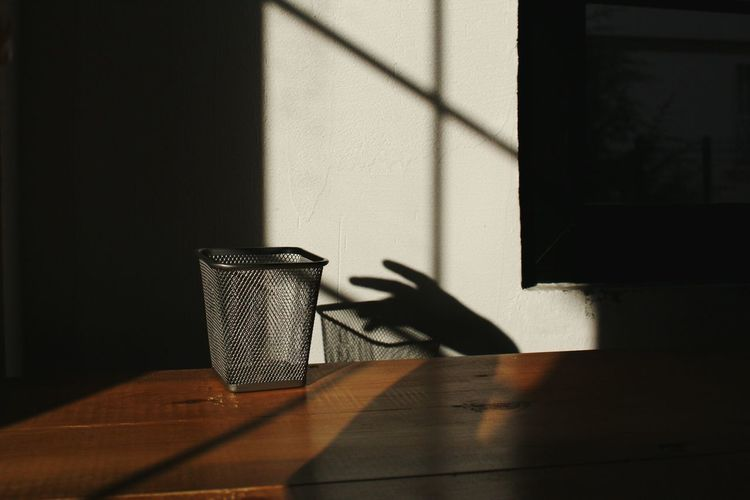 Shadow of person on table against wall
