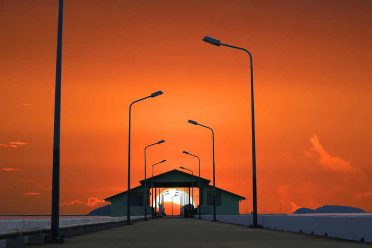 Street lights and built structure against orange sky at sunset