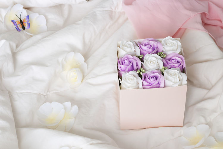 High angle view of white roses on bed