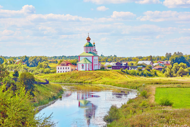 Suzdal summer landscape view with river reflections Suzdal Vladimir Region Famous Cloud Sky Blue White Water Horizon Village Building Houses Field Orthodox Landscape River Reflection Meadow Flower Multi Colored Water Sky Landscape Place Of Worship Religion Spirituality Cross Historic Church Christianity