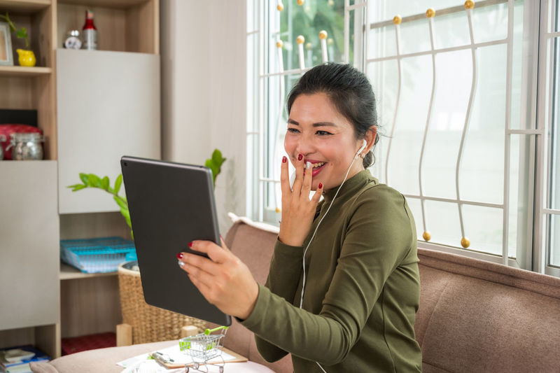Woman using tablet while sitting on sofa