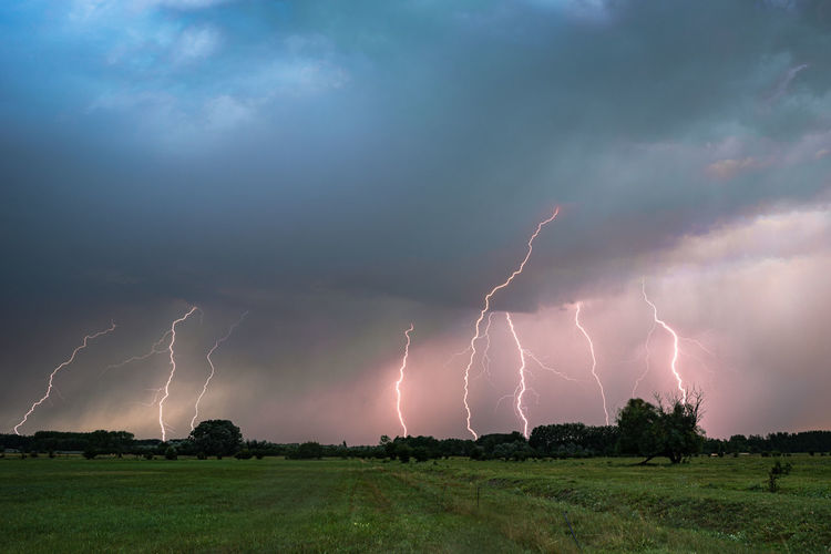 Panoramic view of lightning over landscape against storm clouds