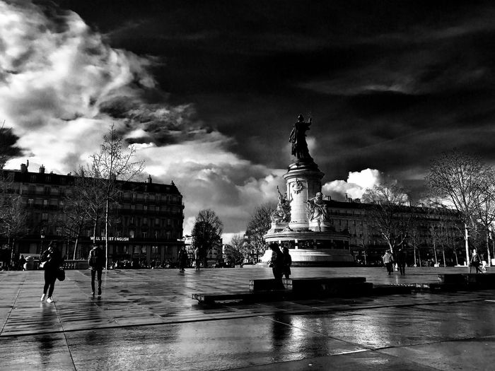 Fountain in city against cloudy sky