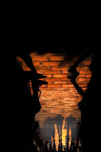 Silhouette people seen through illuminated lamp at night