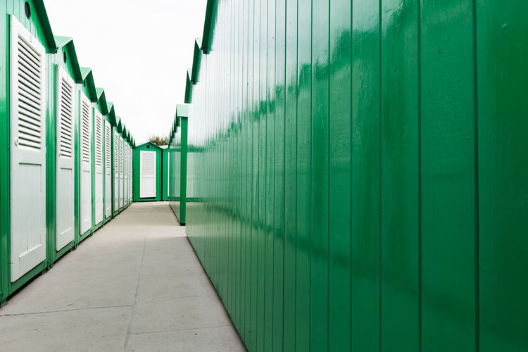 View down a row of green painted wooden beach cabins with white doors