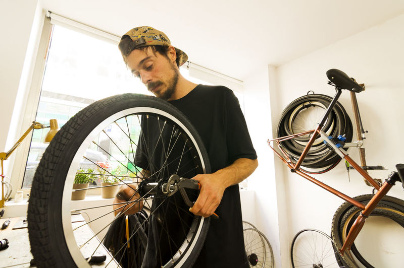 Young Man Repairing Bicycle In Workshop