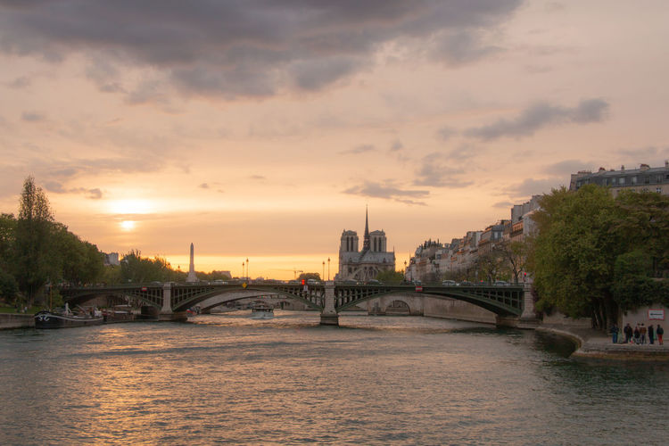 Bridge over river by buildings against sky at sunset