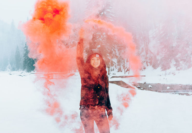 Portrait of young woman holding orange distress flare while standing on snow covered field