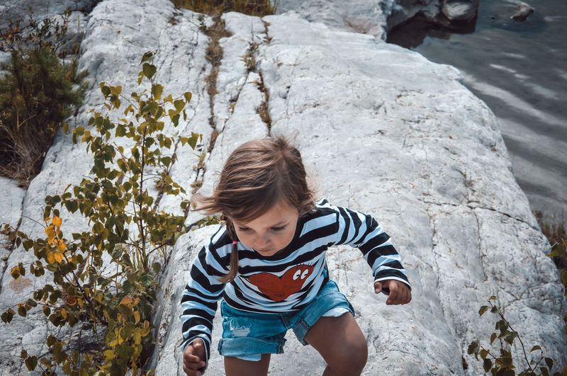 High angle view of boy standing on rock