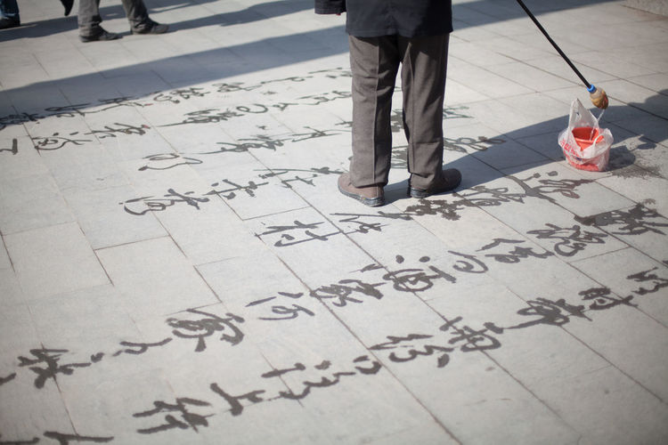 Man doing water calligraphy on sidewalk