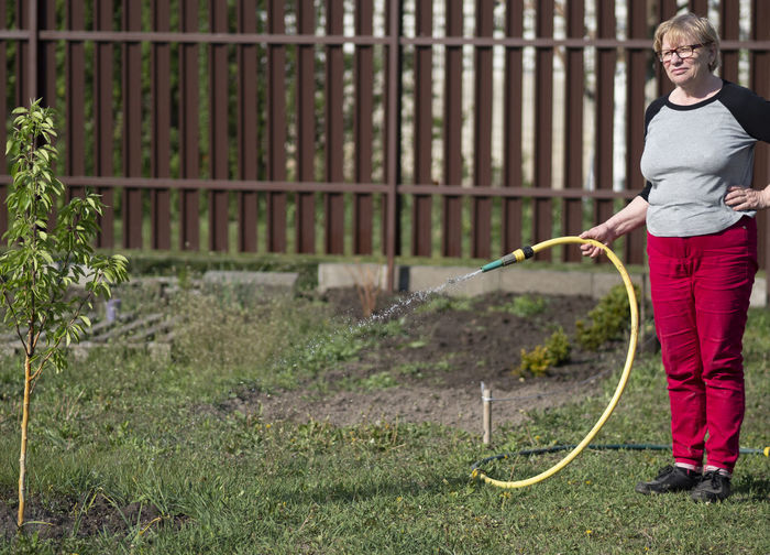 Full length of woman watering plant in lawn