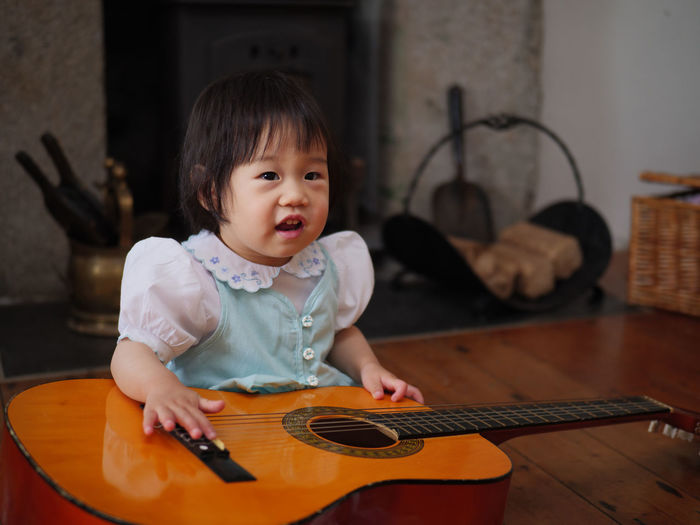 Baby girl sitting with guitar at home