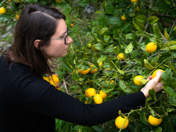 Young woman with fruits growing on plant
