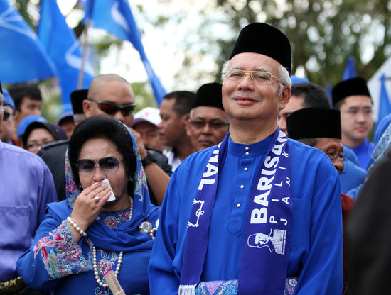 Malaysian Prime Minister Najib Razak and his wife Rosmah Mansor smile during an election campaign in Pekan, Pahang 20 April 2013 1MDB Politics Politics And USA South East Asia Asean Barisan_nasional Blue Crowd Day Election Emotion Event Group Of People Leaders Malaysia Men Muhyiddin Yassin Najib Razak People Personality  Prime Minister Real People Rosmah Mansor Umno Zahid Hamidi