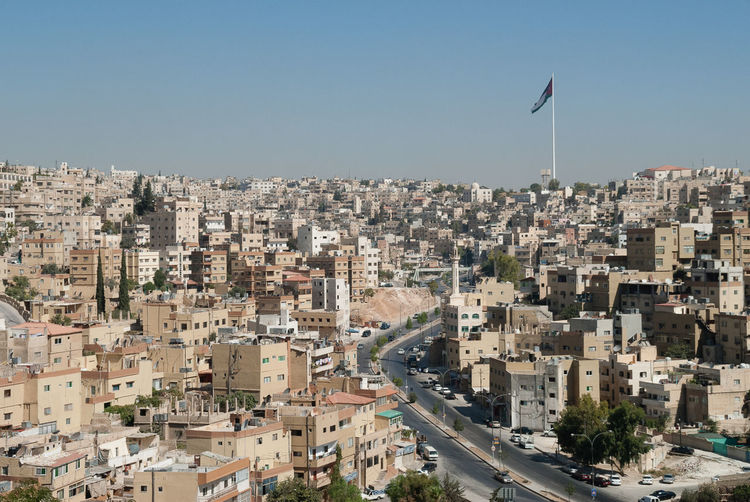 Large flag pole and flag and buildings in amman skyline, jordan