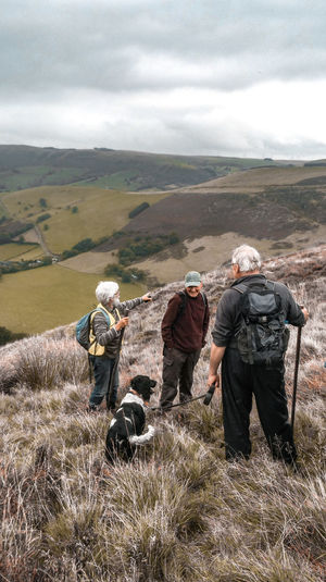 three hikers and a dog Dog Middle Aged Three People Black And White Dog Pointing Hills Wales UK Retirement Grassland Pastures Farmland Countryside Rural Scene Men Mountain Togetherness Sky Landscape Cloud - Sky Hiker Pursuit - Concept Trail Chasing Hiking Backpack Rocky Mountains Explorer Adventure