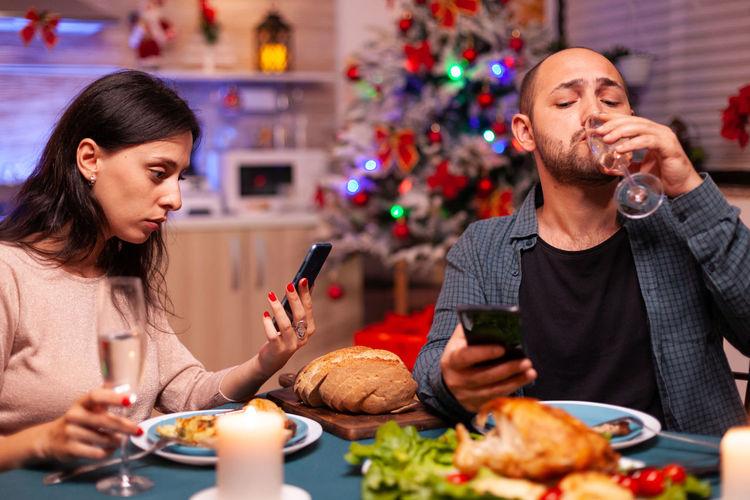 Young man and woman having food on christmas tree