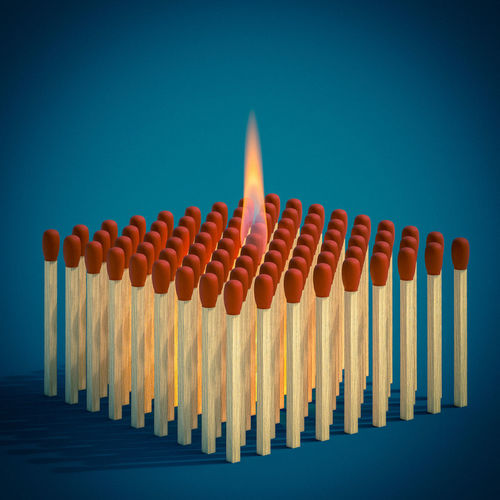 Row of multi colored pencils against blue background