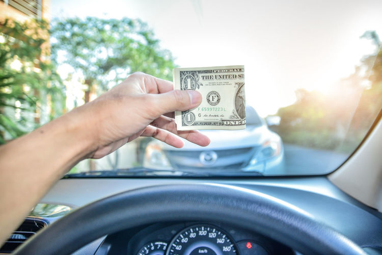 Cropped Hand Of Man Holding Paper Currency In Car