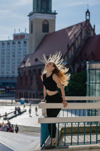 Architecture Beautiful Woman Blond Hair Building Building Exterior Built Structure Clothing Day Fashion Focus On Foreground Hair Hairstyle Leisure Activity Lifestyles One Person Outdoors Railing Real People Tousled Hair Wind Women Young Adult Young Women