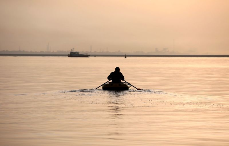 Silhouette man sailing in sea against sky