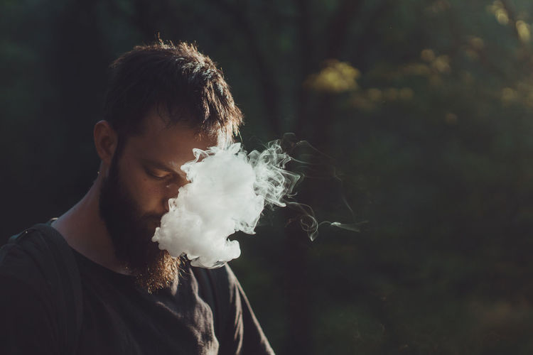 Portrait Spraying Men Concentration Beard Close-up Talcum Powder Face Powder Colliding Magnolia Exploding Particle Jaipur Holi Impact Bubble Wand Blowing Black Background Thoughtful Wearing Hooded Shirt One Mid Adult Man Only Hood - Clothing Entertainment Visual Creativity