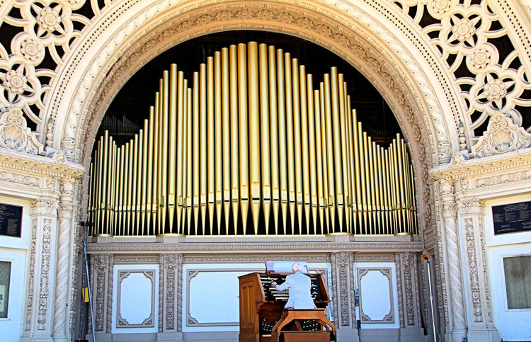 In 2015, the organ was expanded to 80 ranks and 5,017 pipes. San Diego's Spreckels Organ is now the world's largest pipe organ in a fully outdoor venue. Organ pipes are physically organized within the organ according to note and timbre, into sets. A set of pipes producing the same timbre for each note is called a rank, while each key on a pipe organ controls a note which may be sounded by different ranks of pipes, alone or in combination. This is similar to an orchestra which has many different types of instruments, each having its own characteristic sound. If a keyboard of 61 notes controls a group of 10 ranks of pipes, there will be 610 pipes playable from that keyboard. If you understand all that, please explain it to me!! The pipes, range in length from the size of a pencil to 32 feet. There are many more pipes in an organ than the ones you typically see. Organ, Organist, Organ Concert, Organ Pipes, Venue, Pavillion, Pavilion, Balboa Park, San Diego, California,
