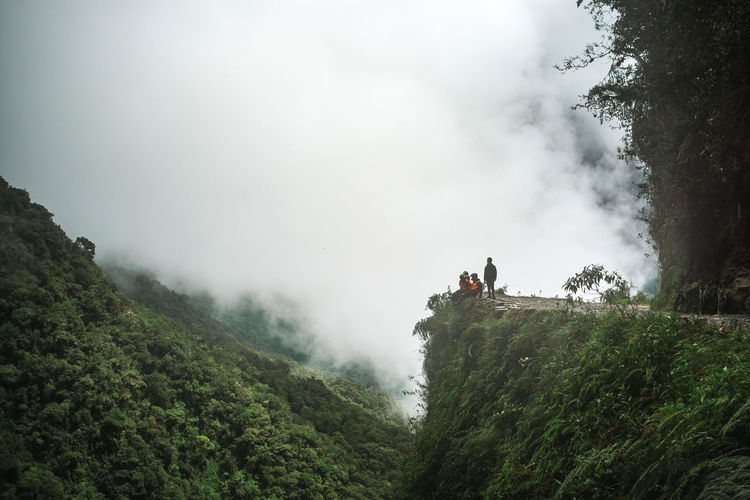 People on cliff against cloudy sky during winter