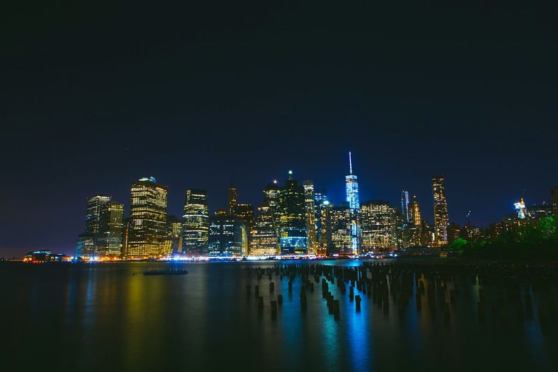 River Against Illuminated Buildings At Manhattan During Night