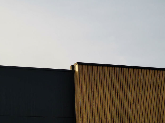 Modern architectural details, wooden wall and black metal wall against sky.