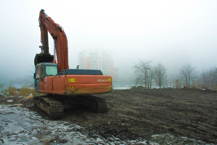 Earthmover at construction site against sky