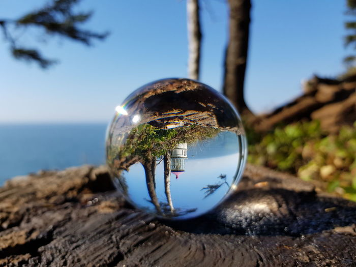 Reflection of crystal ball on glass against blue sky