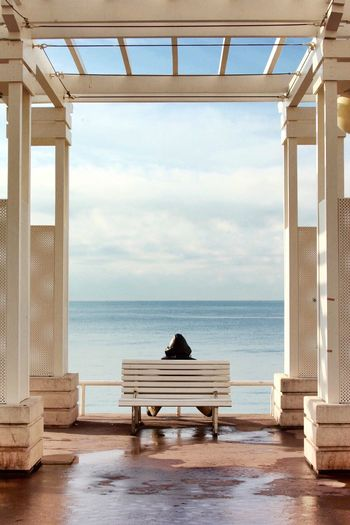 Rear view of man looking at sea while sitting on wooden bench