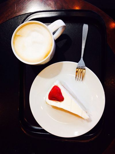 Directly above shot of serving cheesecake slice with coffee on table