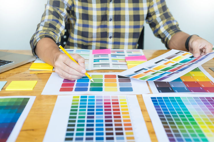 Midsection of man analyzing color swatch in office