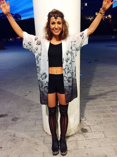 Smiling Young Fashionable Woman With Arms Raised Standing Against Column On Street