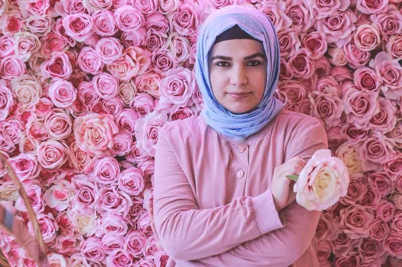 Portrait of woman standing against pink roses