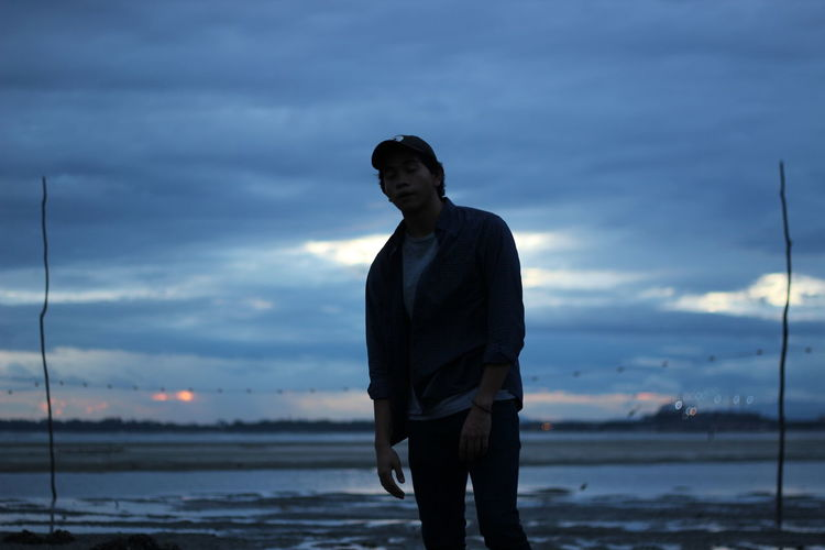 Young man standing at lakeshore against cloudy sky