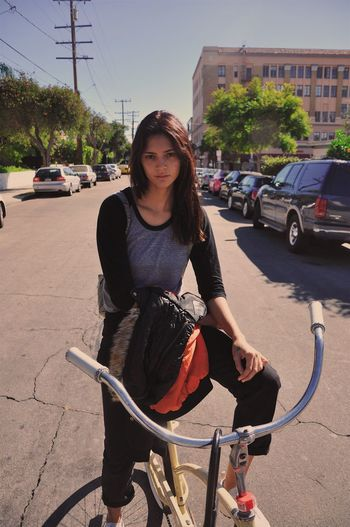 Sophi Transportation Bicycle Land Vehicle Mode Of Transport One Person Car Young Adult Real People Young Women Outdoors Lifestyles Leisure Activity Day Looking At Camera Road Built Structure Tree Beautiful Woman Architecture